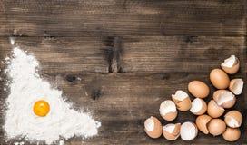 La farina del fondo dell'alimento eggs il tavolo da cucina di legno immagine stock