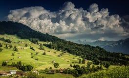 La fattoria ed il granaio alpini su una collina nella sera si accendono contro cielo blu con le nuvole Fotografie Stock Libere da Diritti