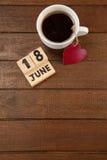 La fecha civil y la taza de café con el corazón forman en la tabla de madera Fotografía de archivo