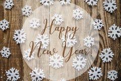 La Feliz Año Nuevo de la inscripción en fondo de madera con los copos de nieve blancos Imágenes de archivo libres de regalías