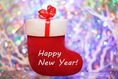 La Feliz Año Nuevo de la inscripción en el regalo rojo sentía la bota en un colore Imagen de archivo