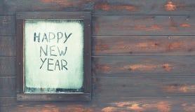 La Feliz Año Nuevo de la inscripción en la ventana escarchada Fotos de archivo