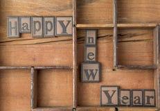 La Feliz Año Nuevo de las palabras en de madera compuesta tipo Fotografía de archivo