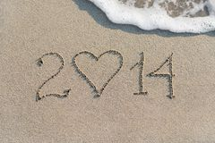 La Feliz Año Nuevo 2014 en la playa arenosa del mar con el corazón, ama concentrado Fotografía de archivo libre de regalías