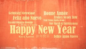 La Feliz Año Nuevo en muchas idiomas en el estuco pintó el fondo de la pared Fotos de archivo libres de regalías