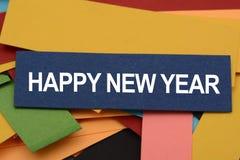 La Feliz Año Nuevo en tarjetas de papel coloridas diseñó para los saludos Foto de archivo