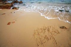 La Feliz Año Nuevo escribe en la playa Fotografía de archivo libre de regalías