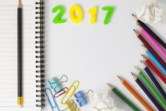 La Feliz Año Nuevo 2017 numera con los materiales de oficina en el escritorio w blanco Imágenes de archivo libres de regalías
