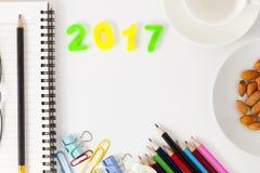 La Feliz Año Nuevo 2017 numera con los materiales de oficina en el escritorio w blanco Imagen de archivo