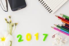 La Feliz Año Nuevo 2017 numera con los materiales de oficina en el escritorio w blanco Fotografía de archivo