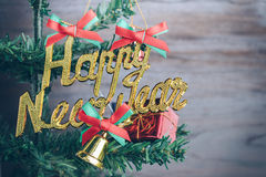 La Feliz Año Nuevo y los ornamentos de la Navidad cuelgan en el árbol de navidad tienen fondo de madera del espacio Foto de archivo