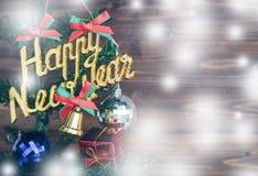 La Feliz Año Nuevo y los ornamentos de la Navidad cuelgan en el árbol de navidad tienen fondo de madera del espacio Imagen de archivo