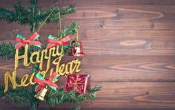 La Feliz Año Nuevo y los ornamentos de la Navidad cuelgan en el árbol de navidad tienen fondo de madera del espacio Foto de archivo libre de regalías