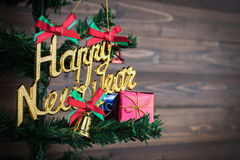 La Feliz Año Nuevo y los ornamentos de la Navidad cuelgan en el árbol de navidad tienen fondo de madera del espacio Fotos de archivo libres de regalías