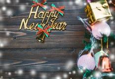 La Feliz Año Nuevo y los ornamentos de la Navidad cuelgan en el árbol de navidad tienen fondo de madera del espacio Imágenes de archivo libres de regalías
