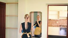 La feliz criada limpia un espejo almacen de metraje de vídeo