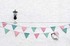 La feliz fiesta de Navidad señala la ejecución del empavesado por medio de una bandera en el fondo blanco de la pared en evento d Foto de archivo