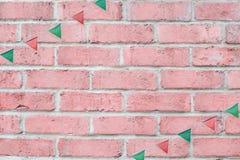 La feliz fiesta de Navidad señala la ejecución del empavesado por medio de una bandera en fondo de la pared de ladrillo del rosa  Imágenes de archivo libres de regalías