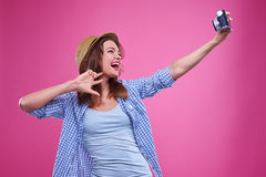 La feliz muchacha está haciendo el selfie usando una cámara retra aislada en el perno Fotografía de archivo