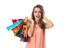 La feliz muchacha guarda la bola detrás de la cabeza y en la otra mano muchos paquetes se aíslan en un fondo blanco Imagenes de archivo