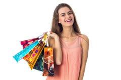 La feliz muchacha ríe y los controles en el suyo dan muchos paquetes se aíslan del fondo blanco Imagen de archivo
