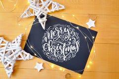 La Feliz Navidad del texto en una pizarra con los deoccrusties de la Navidad protagoniza, guirnalda en fondo de madera de oro End Foto de archivo
