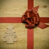 La Feliz Navidad escrita en un árbol de madera y una cinta roja arquean Fotografía de archivo libre de regalías