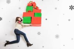 La Feliz Navidad 2017, mamá sostiene muchos regalos para sus niños Imagenes de archivo