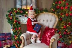 La Feliz Navidad y buenas fiestas muchacha linda del pequeño niño está adornando el árbol de navidad dentro imágenes de archivo libres de regalías