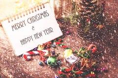 La Feliz Navidad y el año de Happynew mandan un SMS en el cuaderno en blanco con sn Imágenes de archivo libres de regalías