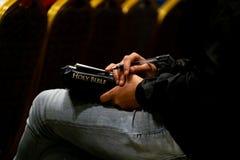 La femelle écoutent le sermon et écrire quelque chose sur le papier avec la bible photographie stock libre de droits