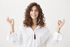 La femelle adulte caucasienne joyeuse positive avec les cheveux bouclés souriant et se tenant dans la pose méditante avec le zen  photo stock