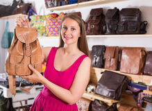 La femelle adulte heureuse dans le centre commercial choisissent le sac à dos Image stock