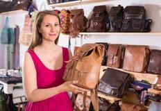 La femelle adulte heureuse dans le centre commercial choisissent le sac à dos Photos libres de droits