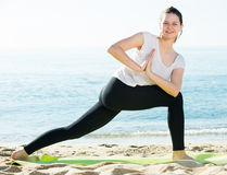La femelle 20-30 années pratique le yoga dans le T-shirt blanc Photo stock