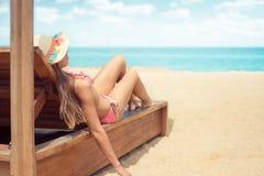La femelle apprécie le bain de soleil se trouvant sur le lit pliant à la plage de sable avec l'océan et au ciel nuageux dans le c photographie stock