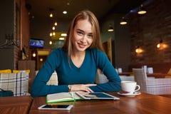 La femelle attend la tablette de reprise pour continuer de travailler dans le réseau Photo stock