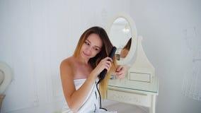 La femelle avec du charme aligne des cheveux utilisant des fers de bordage et des cheveux faits, se reposant sur la chaise Photographie stock libre de droits