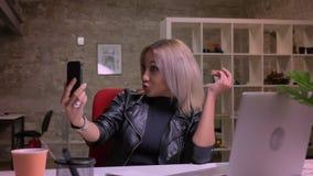 La femelle caucasienne énergique heureuse impressionnante a l'appel visuel tout en se reposant près de son ordinateur portable d' banque de vidéos