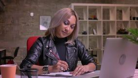 La femelle caucasienne blonde sûre succède la caméra web dans son ordinateur portable tout en reposant et regardant l'écran, briq clips vidéos