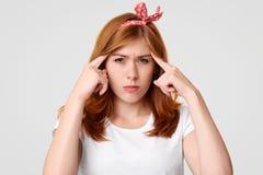 La femelle concentrée sérieuse avec l'expression contrariée, garde les doigts antérieurs sur des temples, essais pour se concentr image stock