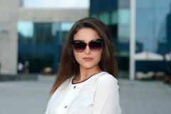 La femelle d'affaires est sur le district des affaires de la ville dans des lunettes de soleil photos libres de droits