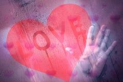La femelle dans l'amour se tient à la fenêtre humide Photo stock