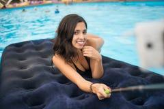 La femelle dans le bikini souriant et fait la photo de selfie au téléphone avec le bâton de selfie sur un matelas dans la piscine photographie stock libre de droits