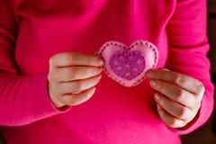 La femelle dans le rose donnent le coeur mou Image stock