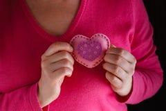 La femelle dans le rose donnent le coeur mou Photographie stock libre de droits