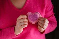 La femelle dans le rose donnent le coeur mou Photo stock