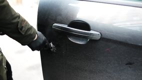La femelle dans la veste avec les gants noirs ouvre la portière de voiture à l'aide du bâton métallique clips vidéos