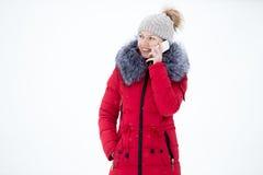 La femelle de sourire heureuse dans la veste rouge d'hiver parle au téléphone portable, Image stock