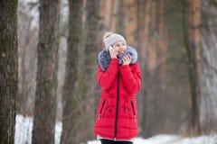 La femelle de sourire heureuse dans la veste rouge d'hiver parle au téléphone portable, Photos libres de droits